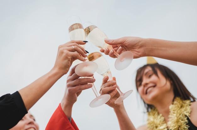 Mulheres felizes animando taças de champanhe na festa no terraço Foto gratuita