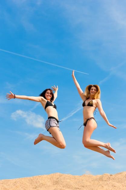 Mulheres felizes em trajes de banho pulando alto acima da areia Foto Premium