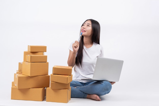 Mulheres felizes que estão pensando no branco blackground online operadores de negócios de compras independente Foto gratuita