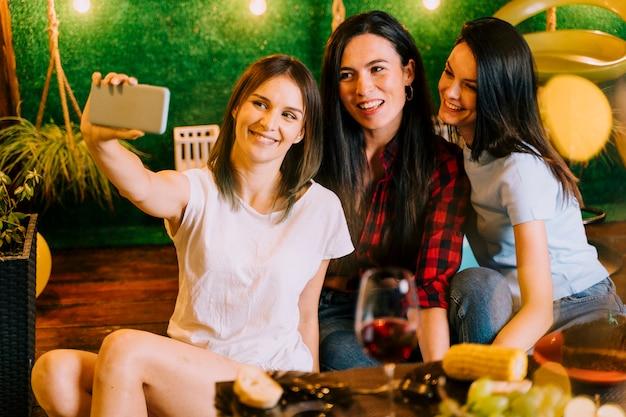 Mulheres felizes tomando selfie na festa Foto gratuita