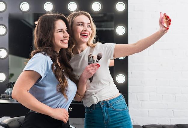 Mulheres felizes tomando selfie no espelho de maquiagem Foto gratuita