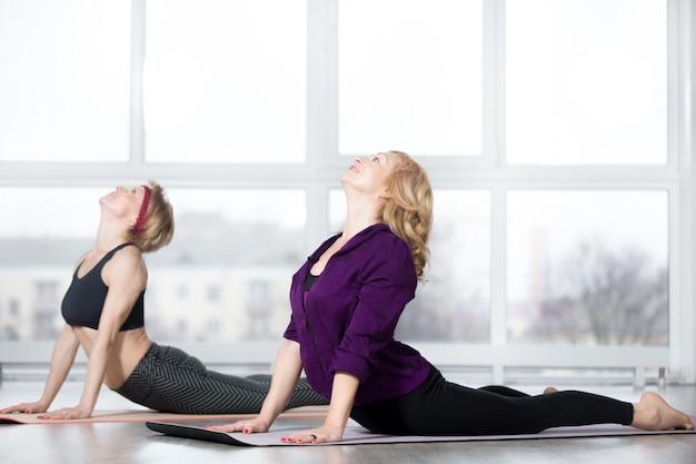 Mulheres idosas fazendo exercícios de alongamento cobra Foto gratuita