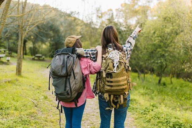 Mulheres irreconhecíveis com mochilas, apontando para a distância Foto gratuita