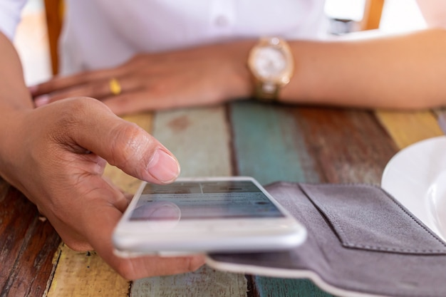 Mulheres jogando jogos eletrônicos no telefone enquanto aguarda pedidos de comida no restaurante Foto Premium