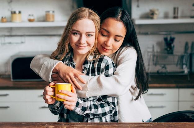 Mulheres jovens, abraçar, em, cozinha Foto gratuita