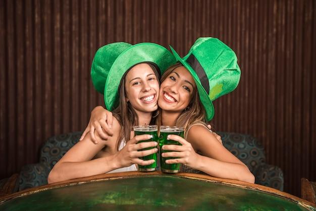 Mulheres jovens alegres abraçando com copos de bebida no sofá perto de mesa Foto gratuita