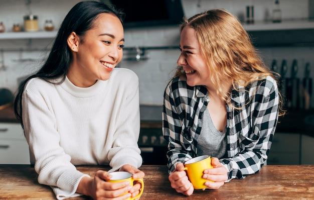 Mulheres jovens, bebendo, chá, e, sorrindo Foto gratuita