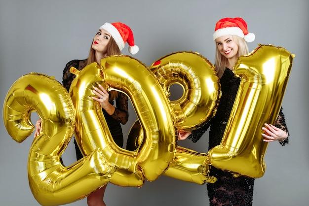 Mulheres jovens com chapéus de papai noel segurando balões dourados Foto Premium