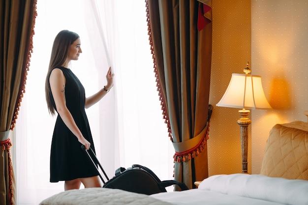 Mulheres jovens com mala estão ficando em um quarto de hotel Foto Premium