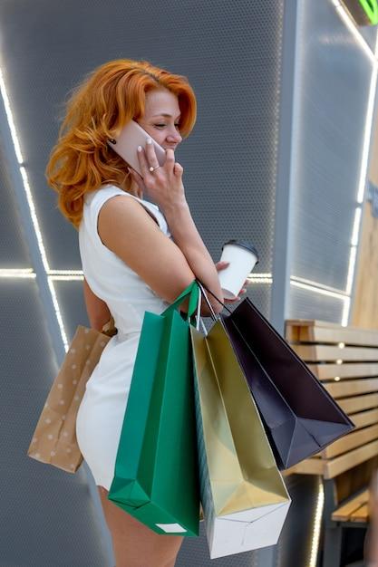 Mulheres jovens com pacotes de compras no shopping moderno Foto Premium