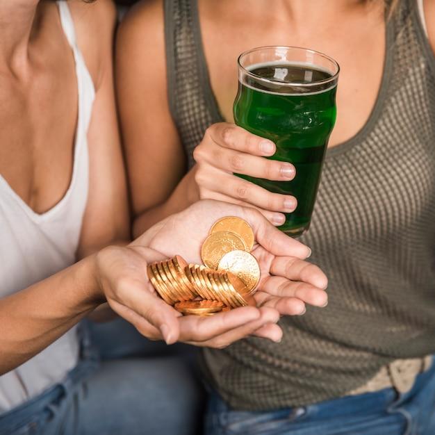 Mulheres jovens, com, vidro, de, bebida, e, montão, de, moedas Foto gratuita