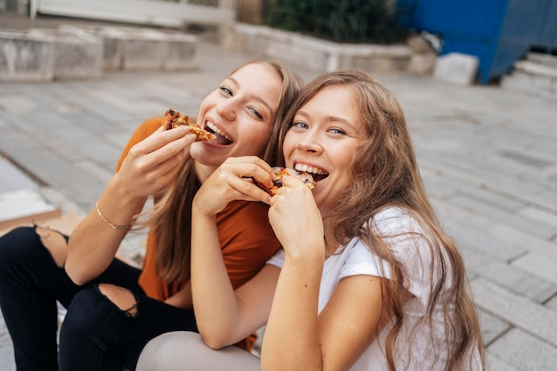 Mulheres jovens comendo pizza juntas Foto gratuita