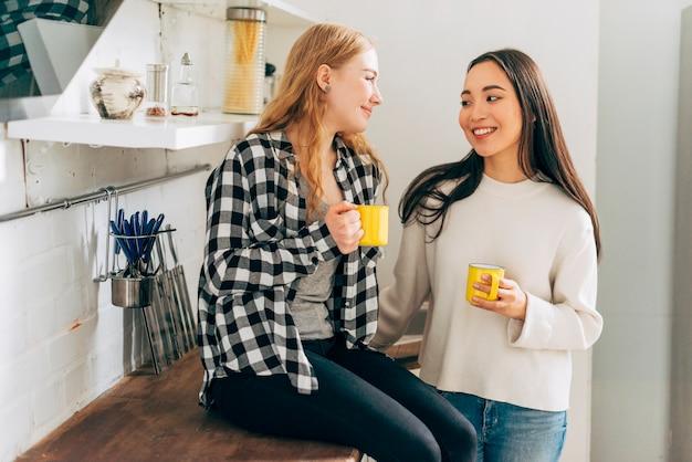 Mulheres jovens, conversando, em, cozinha Foto gratuita