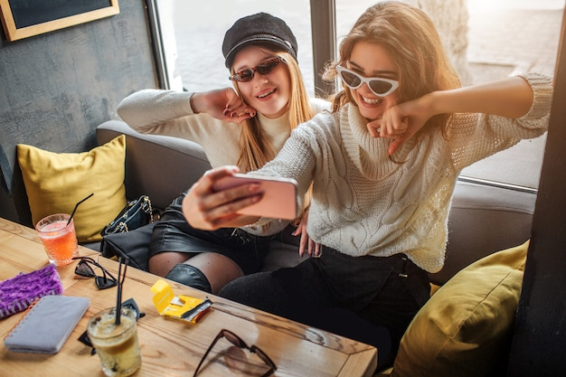 Mulheres jovens elegantes usa óculos escuros e tomam selfie. modelos posam. eles parecem fantásticos. Foto Premium