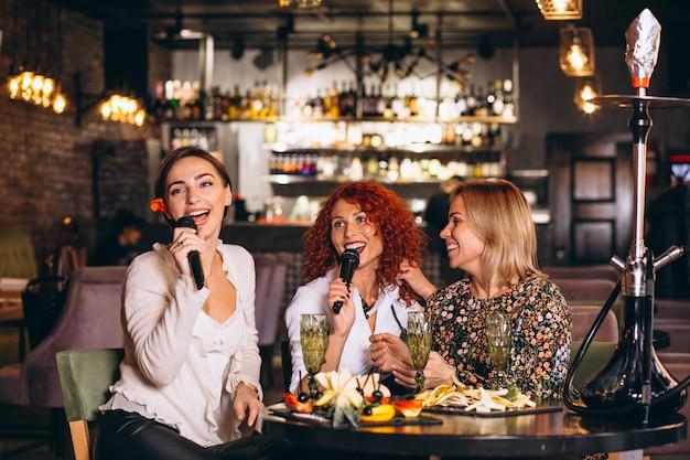 Mulheres jovens, em, um, barra, cantando, karaoke Foto gratuita