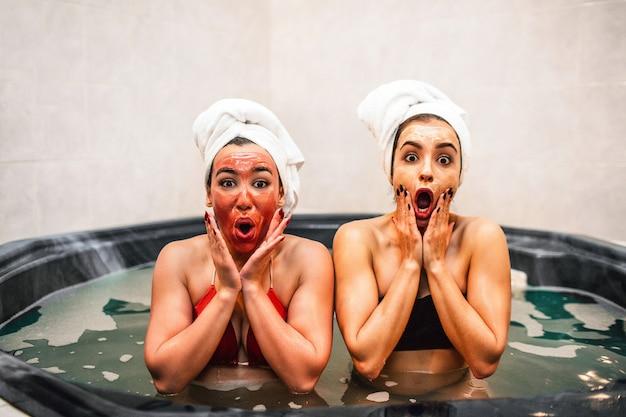Mulheres jovens espantadas sentam-se no banho de hidromassagem e realizam procedimentos de beleza. eles relaxam e relaxam. modelos parecem admirados. eles tocam o rosto com as mãos. Foto Premium