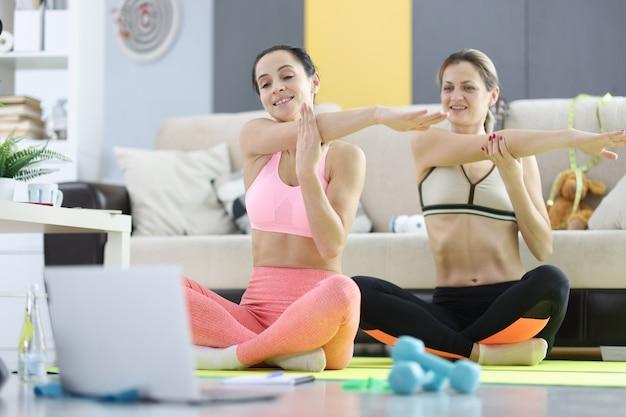 Mulheres jovens fazendo ioga na frente da tela do laptop. conceito de curso de treinamento online Foto Premium