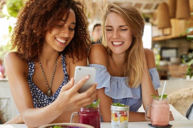 Mulheres jovens felizes assistem um vídeo engraçado na internet no telefone inteligente, sentam-se juntos no interior do café, comem sobremesa saborosa e coquetéis frescos. pessoas, relacionamento e conceito de tecnologia moderna. Foto gratuita