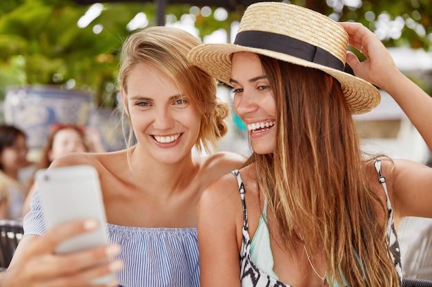 Mulheres jovens felizes assistem um vídeo interessante no telefone inteligente ou fazem selfie, tem um olhar encantado, descansam juntos no refeitório ao ar livre na cidade resort. conceito de pessoas, relacionamento e descanso de verão Foto gratuita