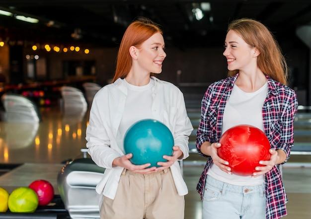 Mulheres jovens felizes segurando bolas de boliche coloridas Foto gratuita