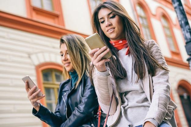 Mulheres jovens, ficar, em, um, urbano, área, usando, telefone móvel, cidade Foto Premium