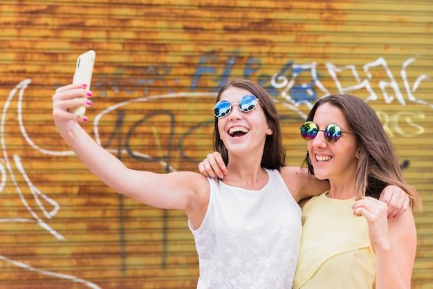 Mulheres jovens, levando, selfie, ligado, smartphone Foto gratuita
