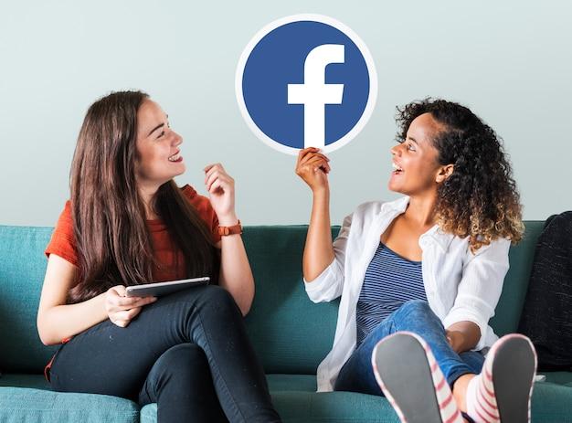 Mulheres jovens, mostrando, um, facebook, ícone Foto gratuita
