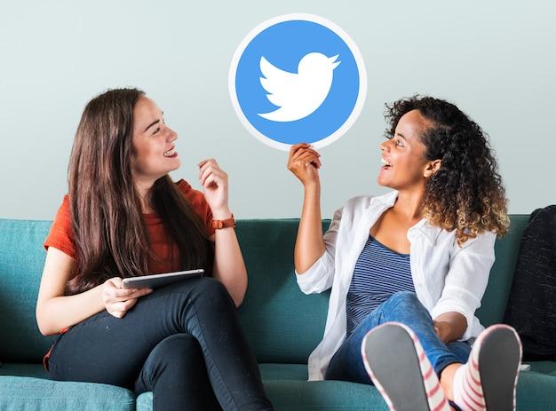 Mulheres jovens, mostrando, um, twitter, ícone Foto gratuita