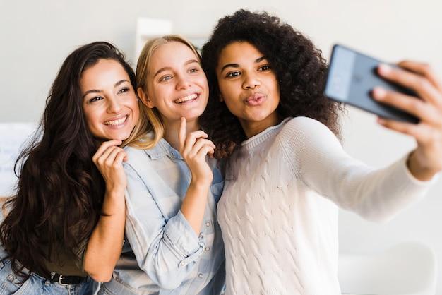 Mulheres jovens no escritório tomando selfies Foto gratuita