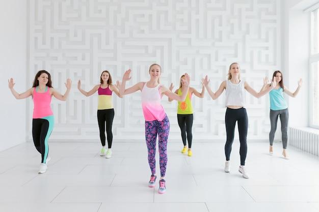 Mulheres jovens no sportswear colorido na aula de fitness dança no estúdio de fitness branco Foto Premium