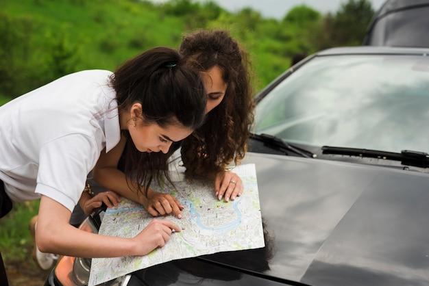 Mulheres jovens, olhando um mapa Foto gratuita