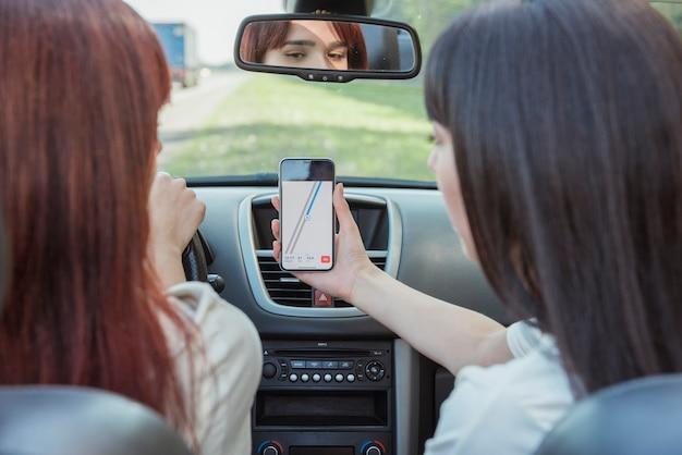 Mulheres jovens, olhar, smartphone, carro Foto gratuita