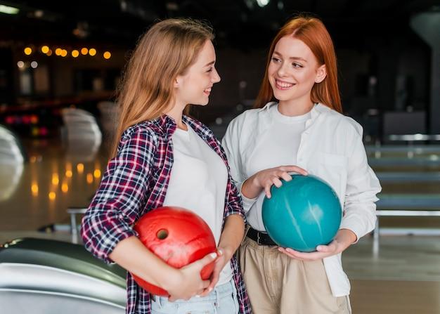 Mulheres jovens, segurando bolas boliche Foto gratuita
