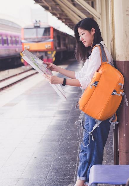Mulheres jovens segurar mapa na mão na estação de trem Foto Premium