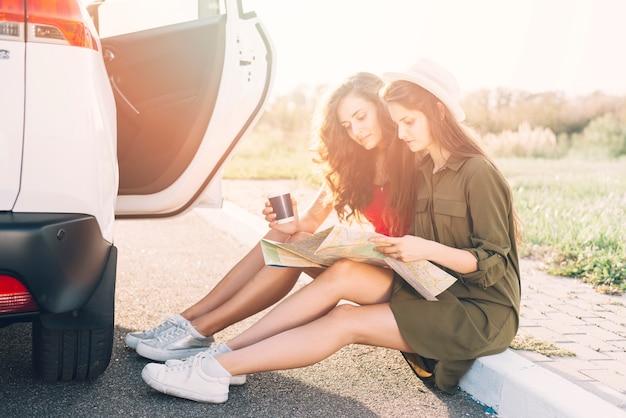 Mulheres jovens, sentando, ligado, borda, com, mapa Foto gratuita