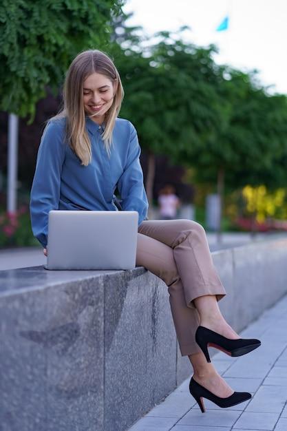 Mulheres jovens trabalhando em um laptop na praça da cidade Foto gratuita