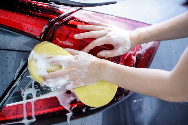Mulheres lavando um carro cinza e sabão com uma esponja amarela. Foto Premium