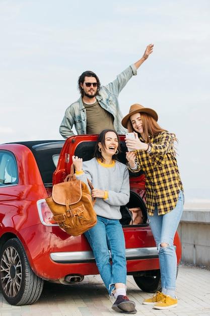 Mulheres, levando, selfie, ligado, smartphone, perto, tronco carro, e, homem, inclinar-se, de, automático Foto gratuita