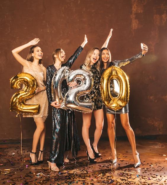 Mulheres lindas comemorando o ano novo. meninas lindas felizes em vestidos de festa sexy elegantes segurando balões de ouro e prata 2020, se divertindo na festa de véspera de ano novo. fazendo selfie ou vídeo para instagram Foto gratuita