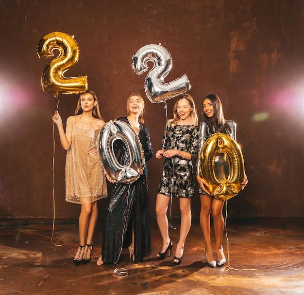 Mulheres lindas comemorando o ano novo. meninas lindas felizes em vestidos de festa sexy elegantes segurando balões de ouro e prata 2020, se divertindo na festa de véspera de ano novo. Foto gratuita