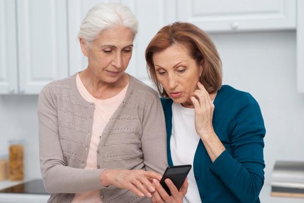 Mulheres maduras, verificando um telefone juntos Foto gratuita