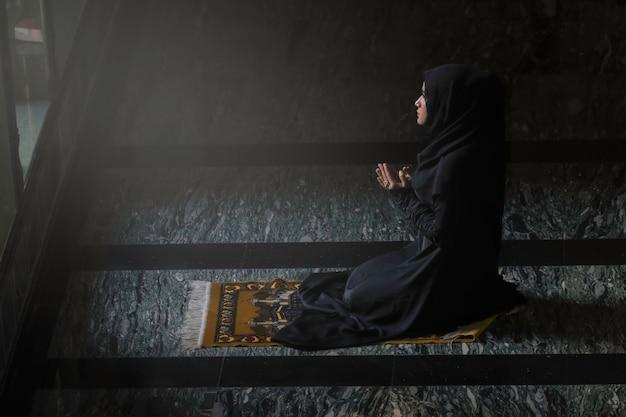 Mulheres muçulmanas vestindo camisas pretas fazendo oração de acordo com os princípios do islã. Foto Premium