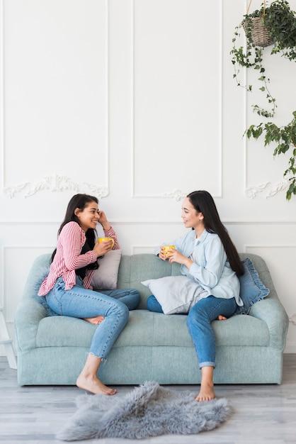 Mulheres multiétnicas, bebendo chá falando no quarto Foto gratuita
