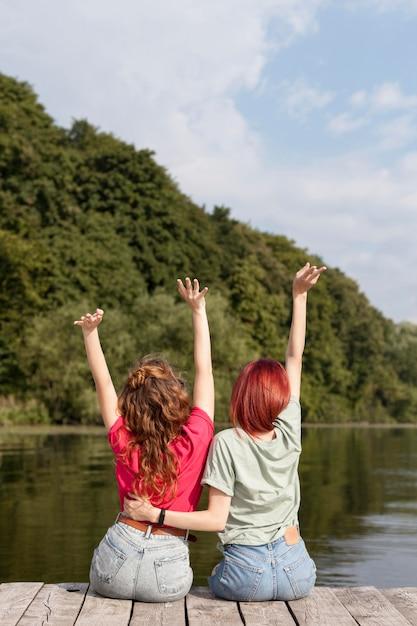 Mulheres na doca com as mãos para o alto Foto gratuita