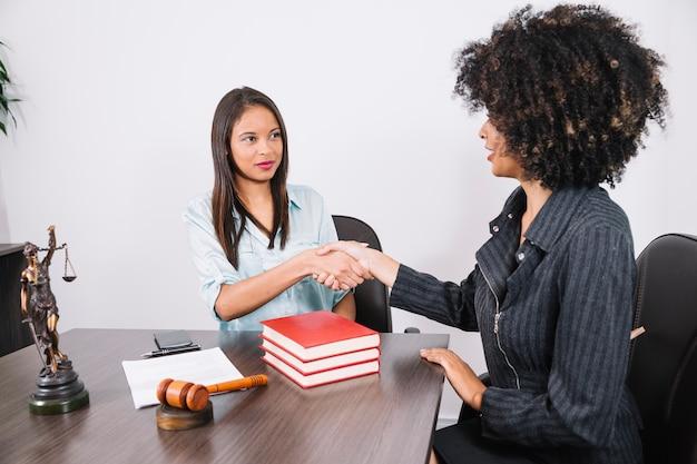 Mulheres negras, apertando as mãos na mesa com livros, smartphone, estátua e documento Foto gratuita