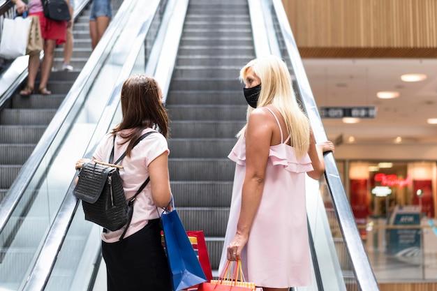 Mulheres no shopping usando máscaras na foto de trás Foto gratuita