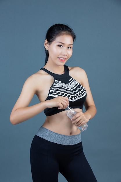 Mulheres no sportswear segurar uma garrafa de água potável Foto gratuita