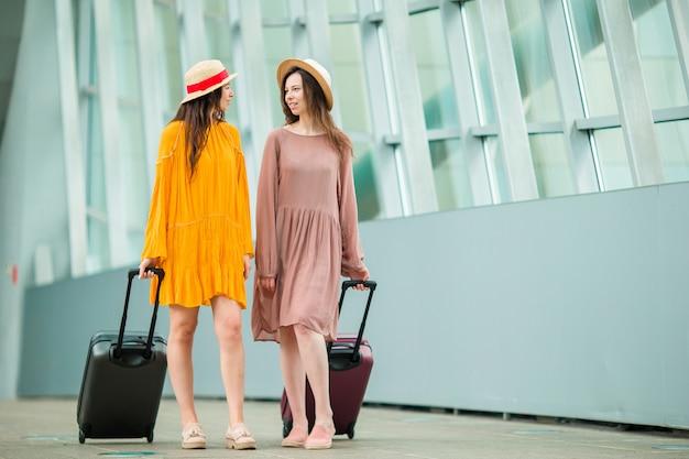 Mulheres novas do turista com bagagem no aeroporto internacional que andam com sua bagagem. Foto Premium