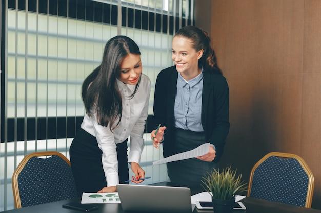 Mulheres, olhar, documentos financeiros, em, laptop, tabela Foto Premium