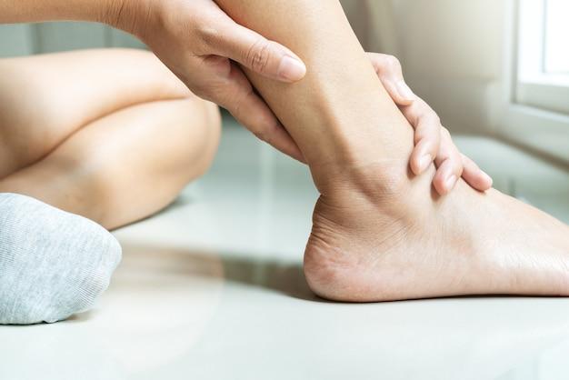 Mulheres perna lesão no tornozelo / doloroso, as mulheres tocam a perna do tornozelo dor Foto Premium